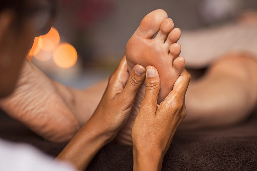 Close up of therapist performing foot reflexology on woman at spa.