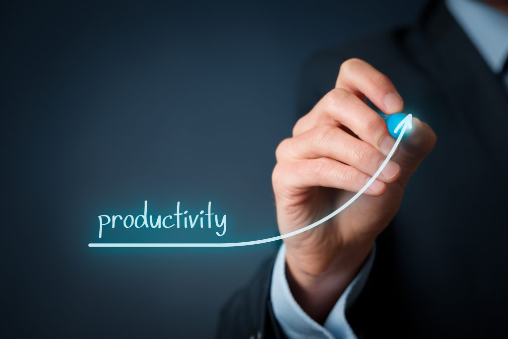 Person in business suit, drawing an arrow going up regarding productivity. Productivity increase concept.