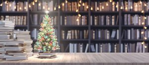 Library desk with Christmas lights and tree with books in the background.