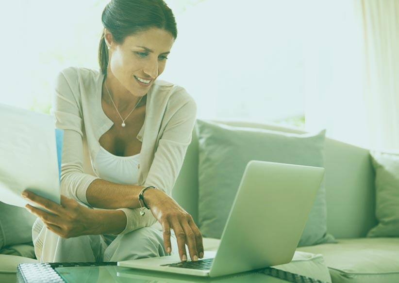 woman sitting on sofa using a laptop